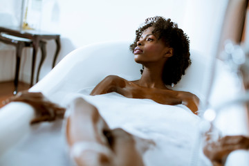 Beautiful african american woman bathing in a tub full of foam