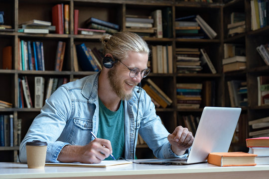 Smiling happy young man wear wireless headset look at laptop screen make notes study e learning in library watch webinar training online course video call, distance education, skype teaching concept