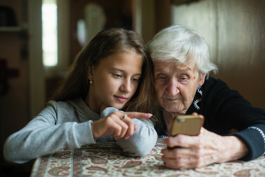 A little cute girl teaches her grandmother to use a smartphone..