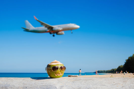 Green coconut wearing sunglasses on the beach in Pumpkin shape for halloween. Vacation concept. Take off plane in the background in defocus.