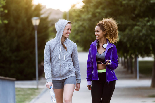 Two smiling sporty young women walking in park after workout