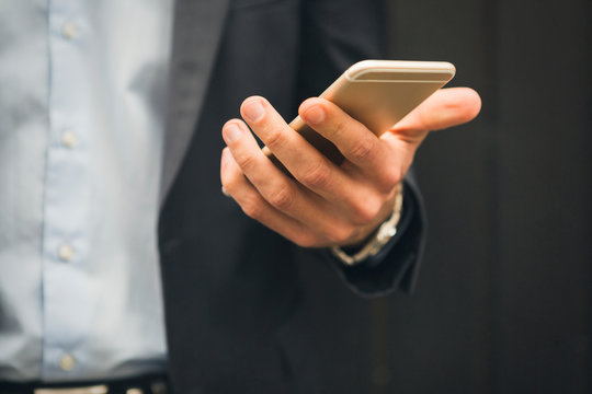 Hand of businessman holding mobile phone, close-up