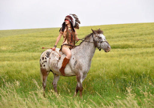 A young Indian girl rides horseback through the prairie. She is dressed up in a traditional Indian costume with  a large feather headdress on her head.