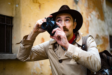 Detective taking pics in a sity slum with his vintage camera