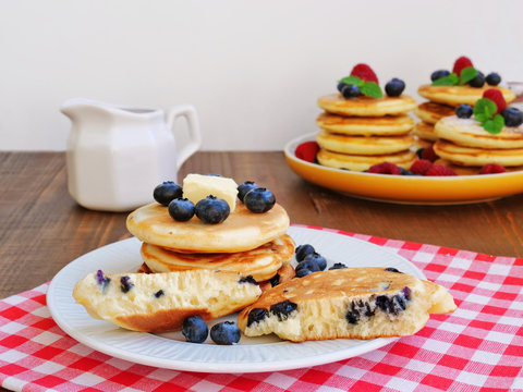 Blueberry mini pancakes with syrup on white plate  over red and white checkered, gingham napkin. Stack of silver dollar pancakes.