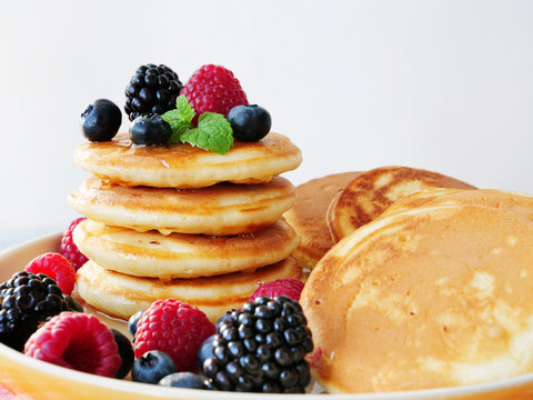 Mini pancakes with raspberries, blueberries and syrup on white plate. Stack of silver dollar pancakes closeup.