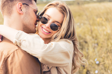 attractive woman hugging and kissing with handsome man in sunglasses