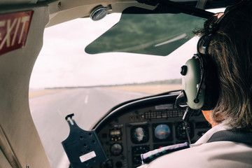 Pilot and dashboard of a small plane on the runway ready to take off
