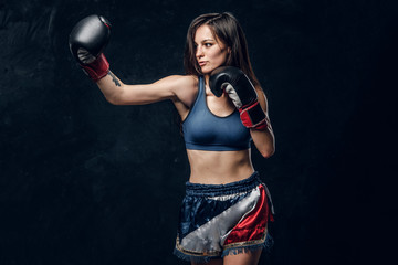 Beautiful female boxer is demonstrating her tactic attack while posing for photographer.