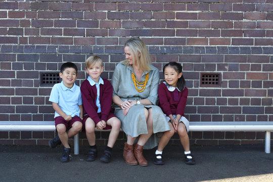 School children and their teacher sitting on bench