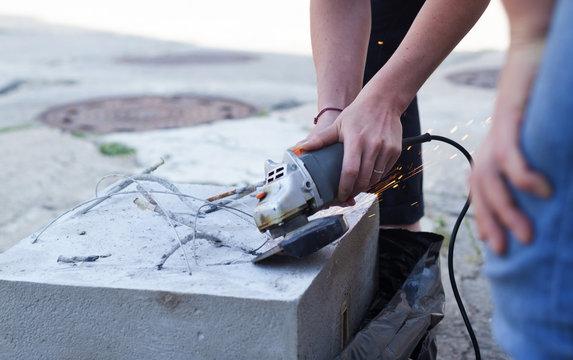 Frau trennt Metall mit einem Trennschleifer Einhand Winkelschleifer Flex von Beton