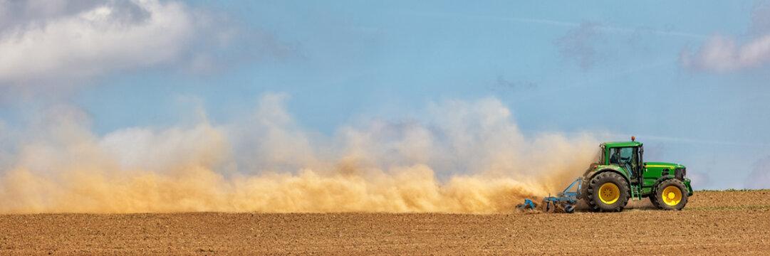 Farmer tilling the soil with disc harrow, Germany