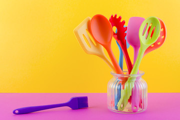 bright multi colored kitchen utensils on yellow background with copy space