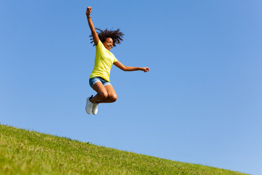 Girl with flying hair jump high on the lawn