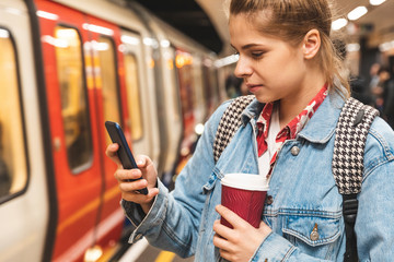 Young woman at subway station using a smartphone Wall mural
