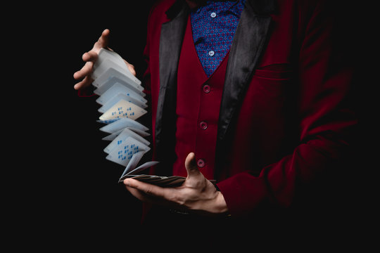 Magician shows trick with playing cards, dark background