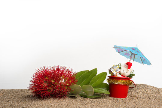 A sprig of red flowering pohutukawa (New Zealand Christmas tree) with Christmas decorations and a cocktail umbrella on sand with a white background.