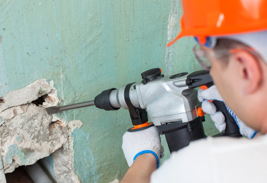 The builder is making hole in wall at construction site with hammer drill perforator equipment.