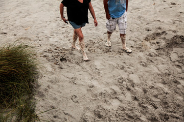 A couple covered with sea foam from beach erosion due to Hurricane Dorian walks towards the parking lot in Jacksonville