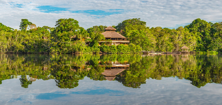 Panoramic rainforest lodge reflection. The tributaries of the Amazon river comprise the countries of Suriname, Guyana, French Guyana, Venezuela, Colombia, Ecuador, Peru, Bolivia and Brazil.