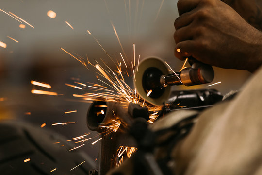 Worker cutting, grinding and polishing motorcycle metal part with sparks indoor workshop, close-up