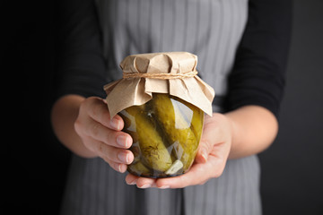 Woman holding jar of pickled cucumbers, closeup view