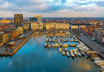 The oldest harbor district of Antwerp city called Eilandje at sunset in use as a yacht marina with waterfront promenade, Antwerp Province, Belgium.