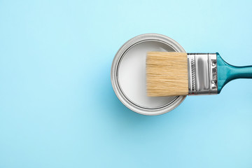 Open can with white paint and brush on blue background, top view. Space for text Wall mural