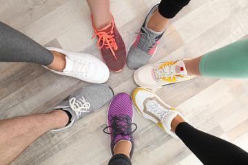 Closeup of athletes wearing sports shoes and standing in circle on wooden floor, top view
