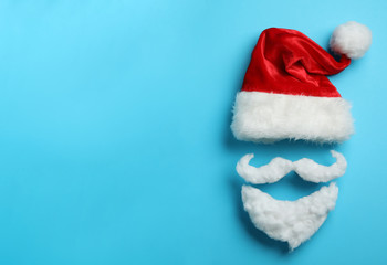 Fotobehang - Santa Claus hat and beard on light blue background, flat lay. Space for text