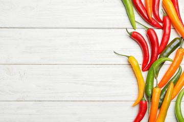 Aluminium Prints Hot chili peppers Different hot chili peppers on white wooden table, flat lay. Space for text