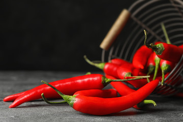 In de dag Hot chili peppers Red hot chili peppers and metal basket on grey table, closeup. Space for text