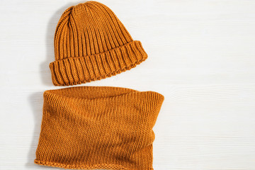 Handmade knitted clothing, woolen hat and soft snood ginger colour. Warm things for winter season. Top view. Copy space. Flat lay.