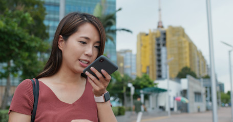 Wall Mural - Woman send audio message on smart phone online at outdoor