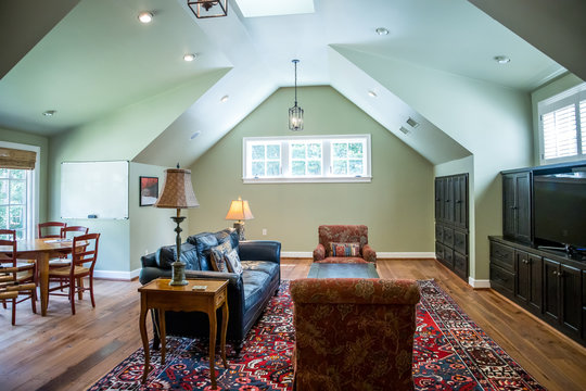 bonus room in an upstairs oft style area painted green with a comfortable couch and arched ceiling design