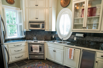 small compact pool guest house kitchen with cream cabinets and stainless steel appliances