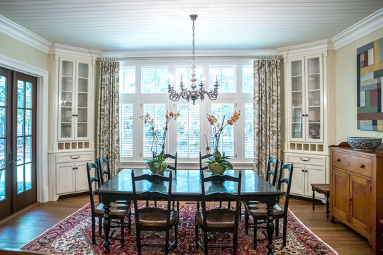 spacious dining room eat in kitchen full of windows and natural light table and chairs  and white shiplap ceiling