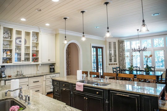 large kitchen with eat-in dining at spacious granite countertop and barstools. Pendant lighting and open kitchen layout.