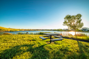 Picnic table at a park with scenic view of a lake that reflects the sky and sun Wall mural