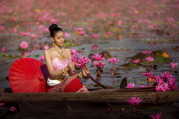 A woman wearing a Thai national costume. She was on a wooden boat to collect the red lotus in the swamp. Reflections on the lifestyles and cultures of ASEAN people.