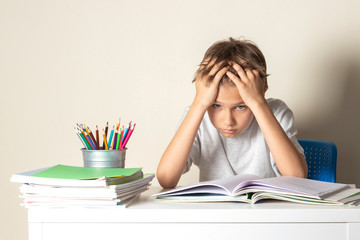 Tired upset schoolboy with pile of school books and notebooks Wall mural
