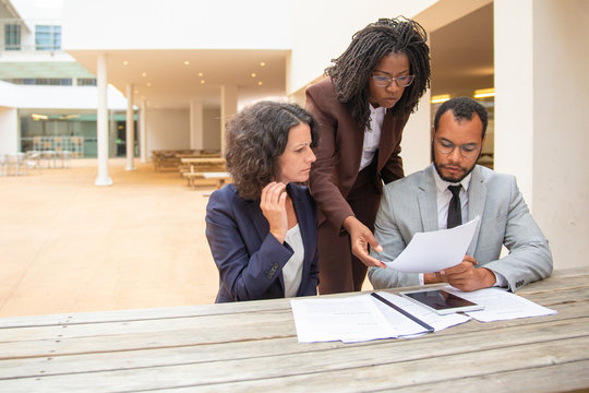 Business team of three studying documents in street cafe. Business man and women sitting and standing at table outside and staring at documents. Paper expertise concept