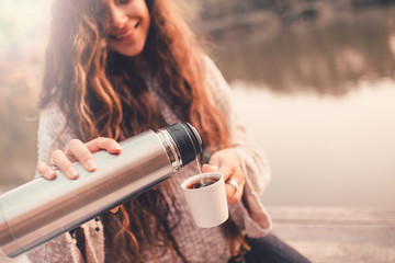 Happy woman in sweater pouring tea from thermos in cup.