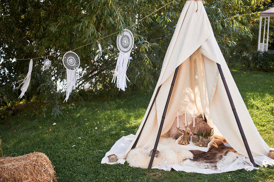 Boho style, wedding decoration. Ease and simplicity. A bamboo hut covered with a linen cloth. Decorative place. Outdoor recreation. Glamping