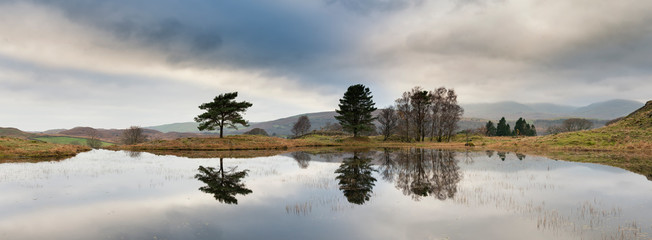 Aluminium Prints Dark grey Stunning landscape image of dramatic storm clouds over Kelly Hall Tarn in Lake District during late Autumn Fall afternoon