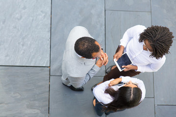 Business team of three discussing work issues near office. Top view of business man and women...