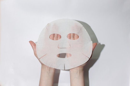 Sheet face mask. Fabric mask for facial skin. Female hands hold a face mask. On a white background. View from above. Cosmetology, medicine and healthcare. The concept of home treatments for moisturiz