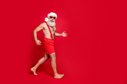 Full length body size view of his he nice attractive cheerful positive glad fit gray-haired man having fun holly jolly running travel isolated over bright vivid shine red background