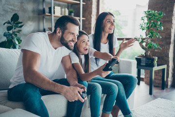 Profile side view of nice attractive lovely cheerful cheery family wearing casual white t-shirts jeans denim sitting on divan having fun video game addicts using gamepad indoors