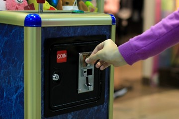 Caucasian girl throws a coin into toy crane vending machine, Claw Game or Cabinet to Catch the Toys. Shopping, holiday activity, game of chance, vacation concept.